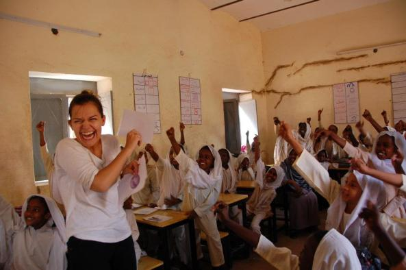 White woman in Sudanese school with many pupils in the room who holding their fist in the air