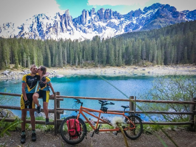 a woman on a wooden fence kissing a man next to a tandem bicycle in front of a mountain lake in the Dolomites