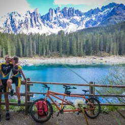 a bicycle rider couple kissing next to a tandem bicycle at a mountain lake