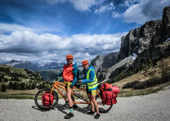 A couple on a tandem orange Velotraum tandem in the Alps