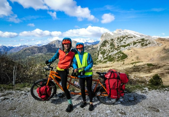 A couple on a tandem orange Velotraum tandem in the Alps - Tips for Traveling by Bicycle