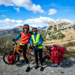 A bicycle rider couple on a tandem bicycle in the mountains