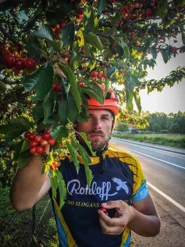 A man eating cherries in the Balkans/ 5 Tips for Traveling by Bicycle