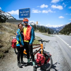a couple in front of a orange tandem bicycle on a pass in the Apls