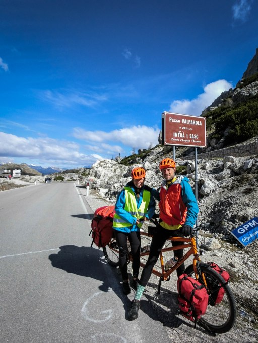 Bicycle rider couple on a tandem bicycle at the Valparola Pass