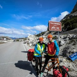 a couple on a orange tandem bicycle on a pass in the Alps