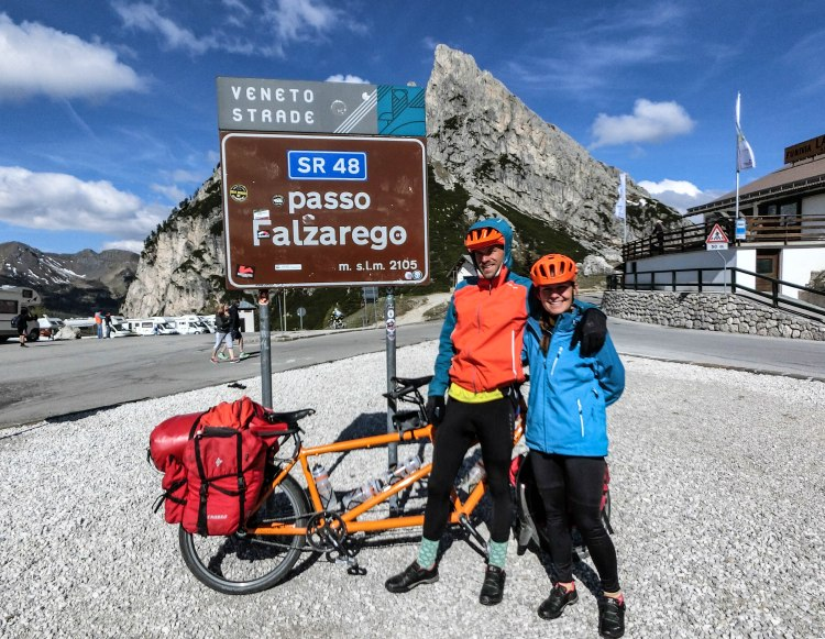 Bicycle rider couple in front of a tandem bicycle at the Falzarego pass