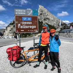 a couple in front of a orange tandem bicycle on a pass at the passo Falzarego