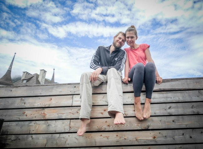 A smiling man and woman sitting next to each other on a wooden bench
