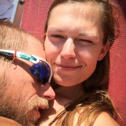 A man with sunglasses sleeping on a smiling women