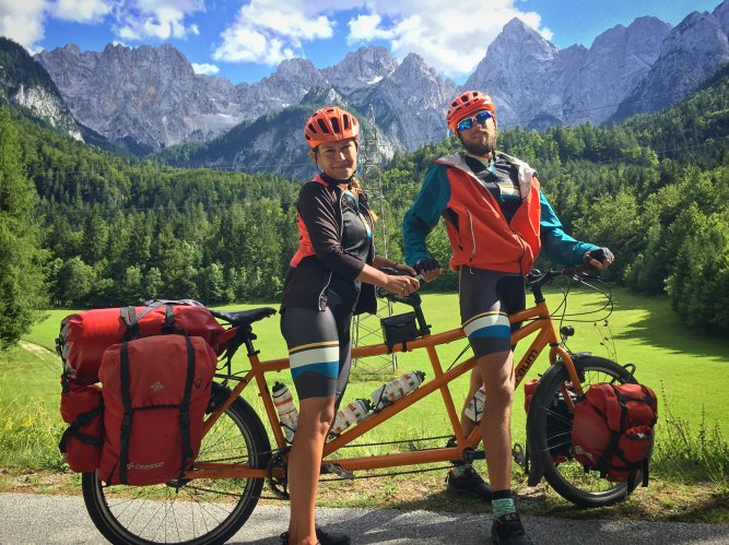A couple on a tandem bicycle in the Alps
