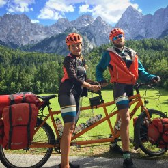 a man and a women on a tandem bicycle in the mountains