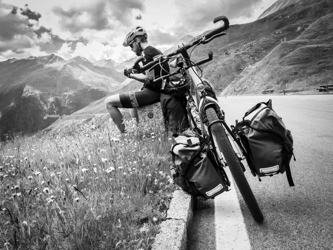 Black and white photo of a male cyclist next a tandem bicycle on the side of the Austrian road