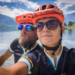 a bicycle couple with orange helmets in front of mountain lake