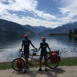 a bicycle couple on a tandem bicycle in front a lake