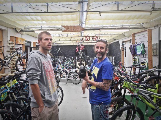 two German man standing in a bicycle shop