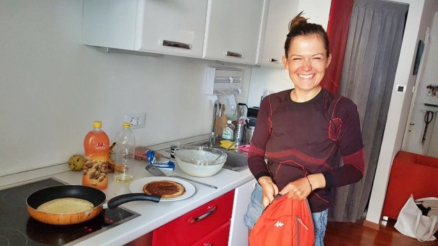 A polish woman holding a red backpack and backing pancakes in a kitchen while Bicycle Touring On a Budget