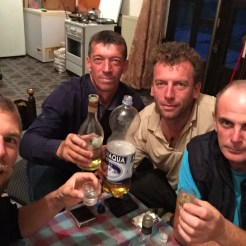 four man sitting on a table drinking alcohol in the Balkans