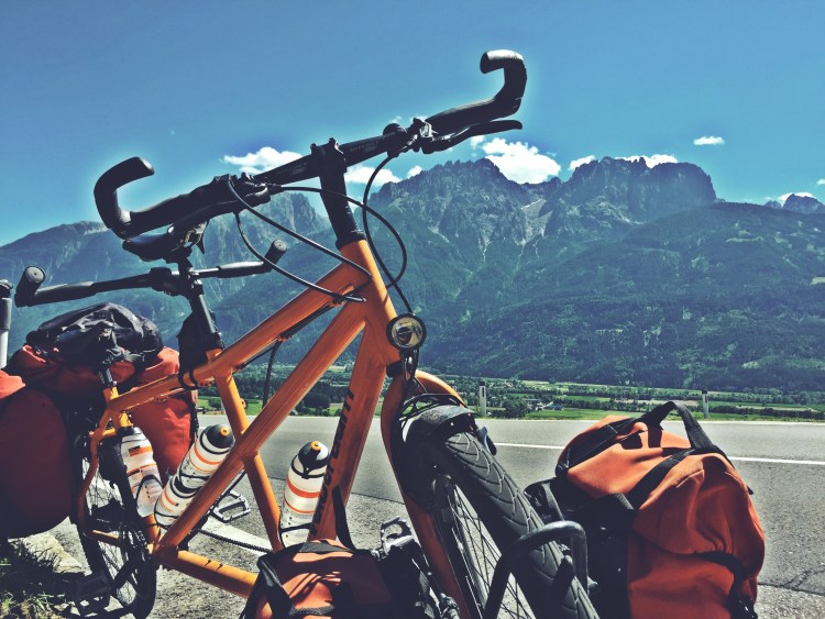 A tandem bicycle on a mountain road in the Alps during Bicycle Touring On a Budget