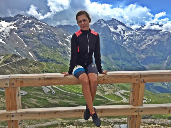Bicycle Touring woman sitting on a wooden fence in the Austrian Alps