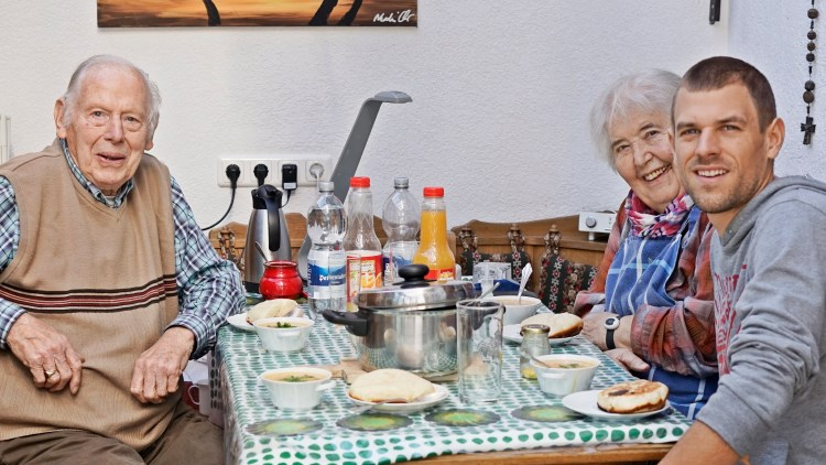 a man with his grand parents sitting on a table eating dampfnudeln