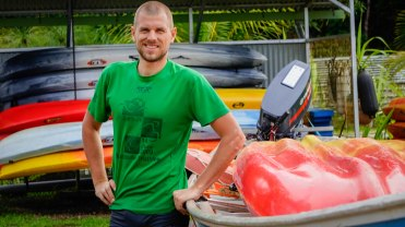 man in green t-shirt in front of kayaks in French Guiana
