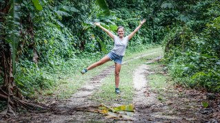 happy female traveler in jungle staying in shape