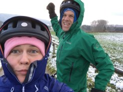 selfie of a female bicycle rider and in the background a male cyclist holding his fist up