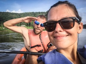 a saluting man and a smiling woman on a kayak