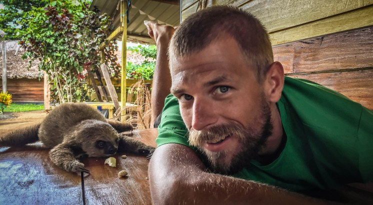 Man next to a sloth
