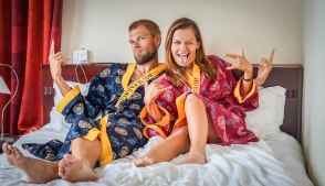 a happy couple with bath robes on a hotel bed having fun