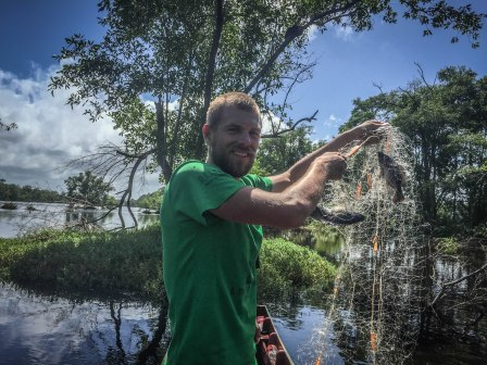 a man on a boat holding a fishing net with fish