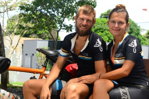 man and woman sitting on a bench next to tandem bicycle / Cycling through South America
