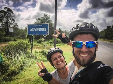 a couple showing the peace sign in front of a street sign / Cycling through South America