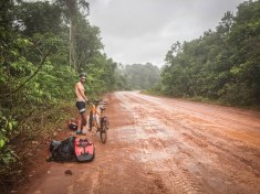 Man next to a tandem bicycle in the jungle in Guyana / Cycling through South America