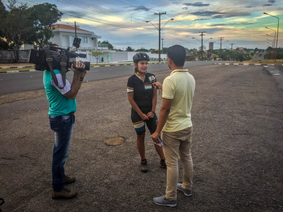 A man interviewing a female bicycle rider and a man filming in Boa Vista, North of Brazil