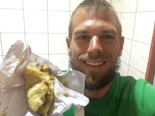 smiling man eating Doubles in Trinidad food