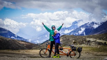 happy couple on a tandem bicycle in the mountains / Cycling through South America