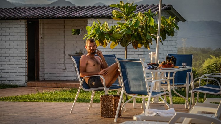 A blonde topless man sitting on a chair on a table in the garden
