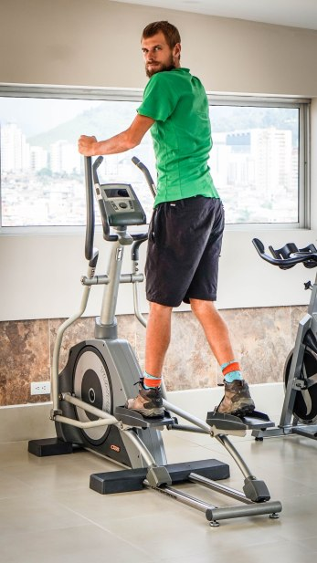 A blonde man wearing black shorts and a green T-shirt working out on a cardio stepper in a gym