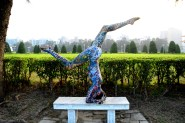 Painted woman doing a hand stand on a table