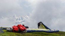 A man laying out a paraglider on a cloudy hill