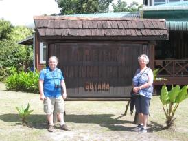 "An American couple in front of a sign which says ""Kaieteur National Park"""