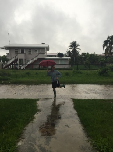 A woman standing on the street with an umbrella in Guyana during the rain