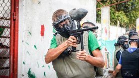 Man shooting a paint ball gun