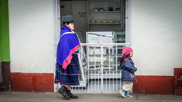 A woman and a girl walking passed a store in Silvia, Colombia