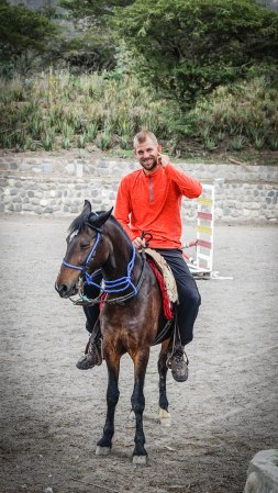 smiling man wearing a red long sleeve riding a horse