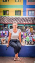 A smiling woman sitting on a wall in Guatape