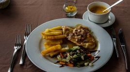 a plate with french fries, vegetables and chicken