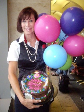A woman holding a cake and balloons / Flight Attendant Lifestyle